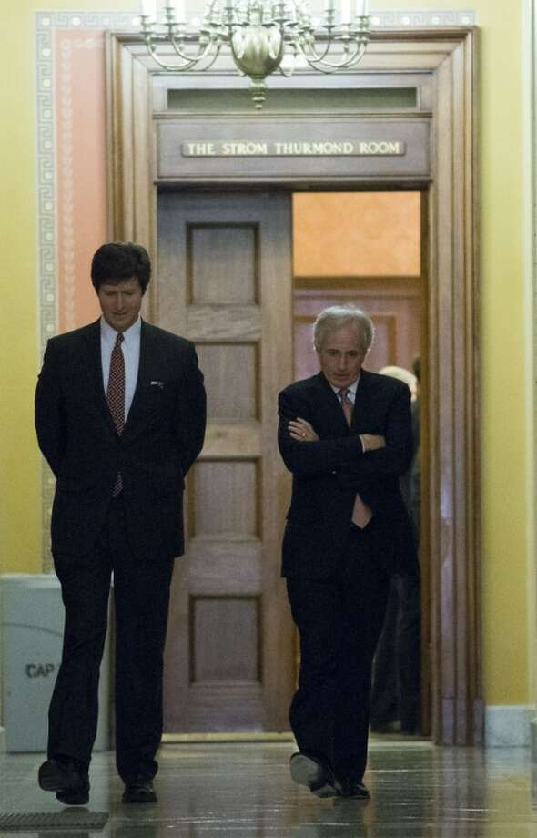 Sen. Bob Corker, R-Tenn., right, departs the Strom Thurmond room, with an aide, after a Senate Republican caucus meeting about the fiscal cliff, on Capitol Hill Monday, Dec. 31, 2012 in Washington. (AP Photo/Alex Brandon)