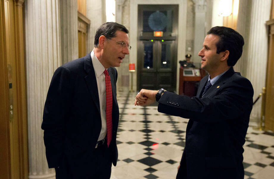 Sen. John Barrasso, left, R-Wyo., talks with Sen. Brian Schatz, D-Hawaii, who holds up his watch, near the Senate chambers after a vote on the fiscal cliff, on Capitol Hill Tuesday, Jan. 1, 2013 in Washington. The Senate passed legislation early New Year's Day to neutralize a fiscal cliff combination of across-the-board tax increases and spending cuts that kicked in at midnight. (AP Photo/Alex Brandon) / AP