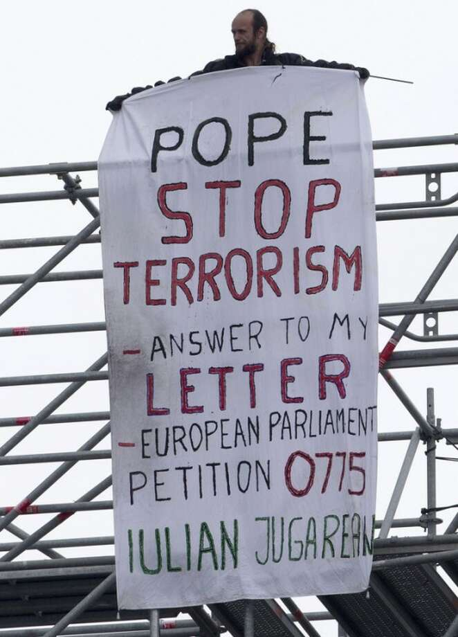 "A man identified as Julian Jungarean stands on scaffolding displaying a banner during during a New Year's Day Mass celebrated by Pope Benedict XVI in St. Peter's Basilica at the Vatican, Tuesday, Jan. 1, 2013. A man has scaled the scaffolding around St. Peter's Square and draped a banner calling on Pope Benedict XVI to ""Stop Terrorism."" The man identified himself on the banner as Julian Jungarean, a Romanian who has previously scaled the Bernini colonnade around the piazza. (AP Photo/Andrew Medichini)"