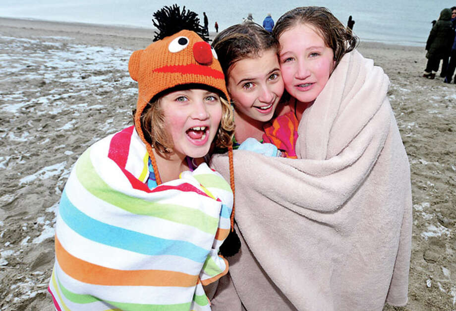 Allison Pavloff, 10, Gabrielle, Rodia, 10 and Michelle Pavloff, 12, warm up after particip[ating in the Team Mossman Triathlon Club's 10th annual 'polar plunge' at Compo Beach Tuesday to benefit Save the Children. Hour photo / Erik Trautmann / (C)2012, The Hour Newspapers, all rights reserved