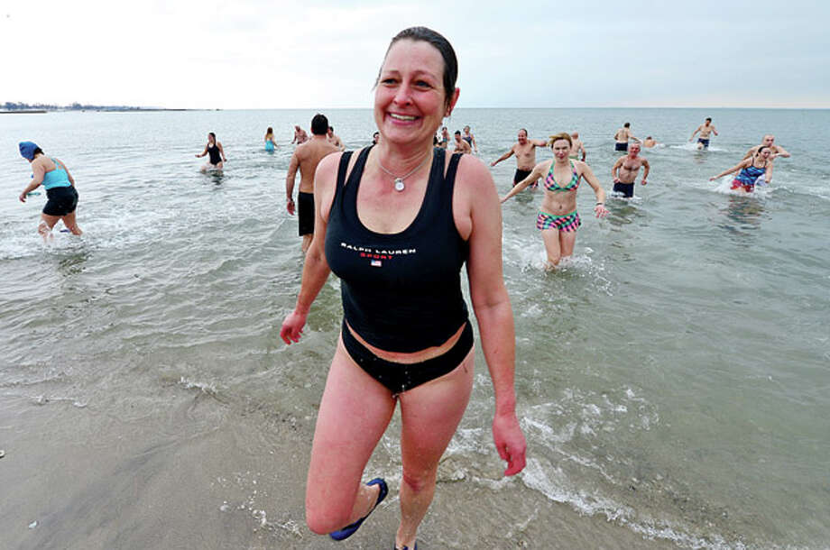 Team Mossman Triathlon Club member and Norwalk resident Kate Stoker kicks off the New Year with the club's 10th annual 'polar plunge' at Compo Beach Tuesday to benefit Save the Children. Hour photo / Erik Trautmann / (C)2012, The Hour Newspapers, all rights reserved