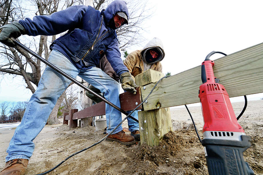 Damage from Hurricane Sandy is still apparent Tuesday as Tony Duarte and Roman Vasquez of Total Fence repair fencing at Calf Pasture Beach. Hour photo / Erik Trautmann / (C)2012, The Hour Newspapers, all rights reserved