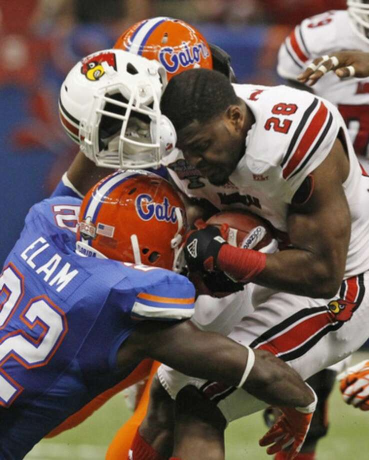 Louisville running back Jeremy Wright (28) loses his helmet to a hit by Florida defensive back Matt Elam (22) in the second half of the Sugar Bowl NCAA college football game Wednesday, Jan. 2, 2013, in New Orleans. (AP Photo/Butch Dill)