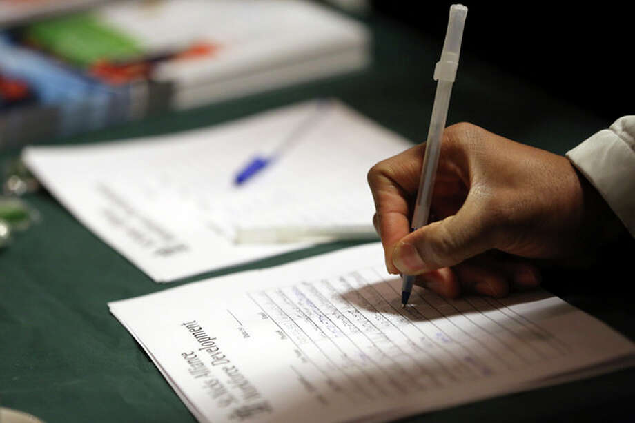 In this Wednesday, Dec. 12 2012 photo a job seeker leaves his contact information with a potential employer during a job fair in New York. More Americans sought unemployment benefits in the last week of 2012, though the winter holidays likely distorted the data for the second straight week. (AP Photo/Mary Altaffer) / AP