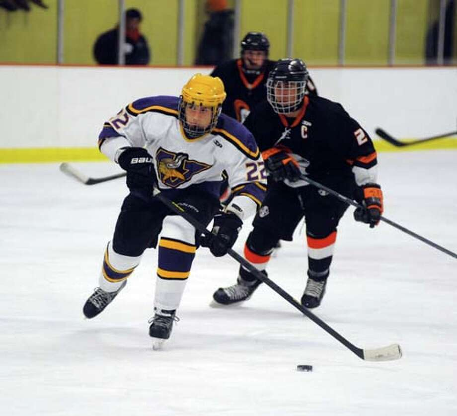 Hour photo/John Nash - Westhill's Evan Shaulson (22) skates up ice in front of Stamford's Andrew Tuccinardi.