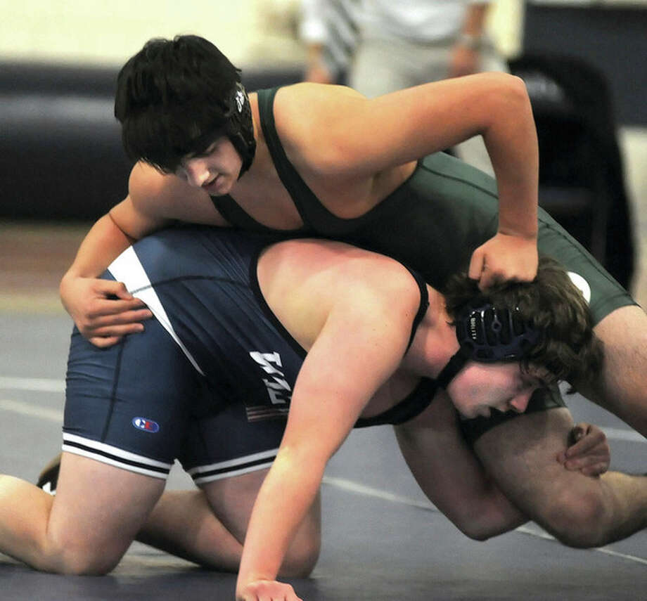Hour photo/John NashNorwalk's Sam Patterson, top, tries to get a better hold on Wilton's Kieran Reardon during their 195-pound wrestling match at the Zeoli Field House in Wilton on Thursday. Patterson won a 10-9 decision.