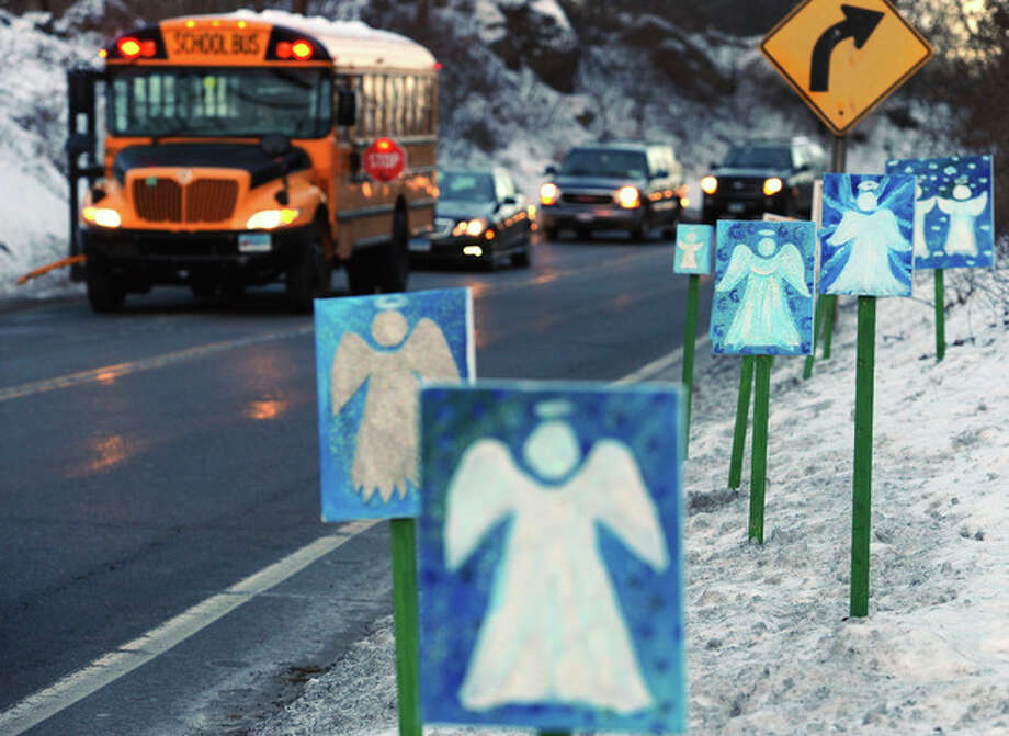 A bus traveling from Newtown, Conn., to Monroe stops in front of 26 angels along the roadside on the first day of classes for Sandy Hook Elementary School students since the Dec. 14 shooting, in Monroe, Conn., Thursday, Jan. 3, 2013. Chalk Hill School in Monroe was overhauled especially for the students from the Sandy Hook School shooting. (AP Photo/Jessica Hill) / FR125654 AP