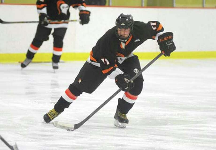 Hour photo/John Nash - Stamford's Mike Rybl looks up ice as he skates with the puck during Wednesday's game against Westhill at the Terry Conners Rink.