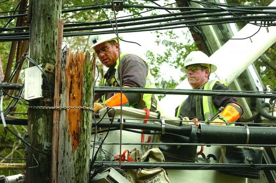 Crews work on repairing a snapped utility pole.