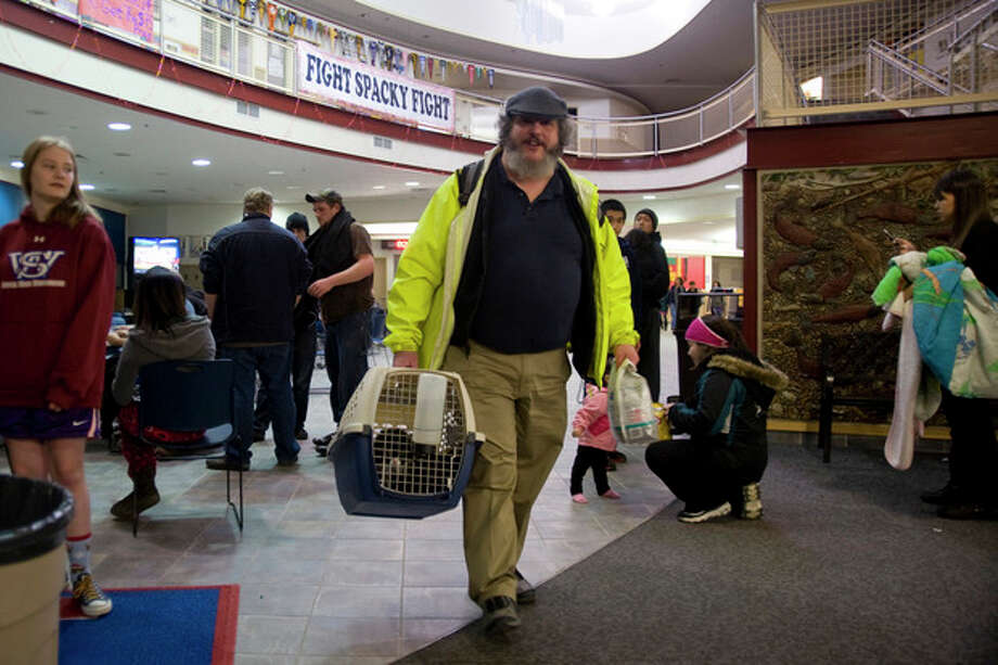 Charles Bingham heads back home with his cats after a tsunami warning was canceled early Saturday, Jan. 5, 2013, in Sitka, Alaska, following a magnitude 7.5 earthquake. (AP Photo/Daily Sitka Sentinel, James Poulson) / Daily Sitka Sentinel