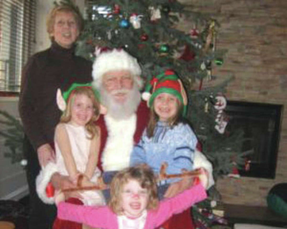 Lomer Johnson, in Santa suit, his wife Pauline and their three grandchildren, 9-year-old Lily and 7-year-old twins Grace and Sarah. Contributed photo.