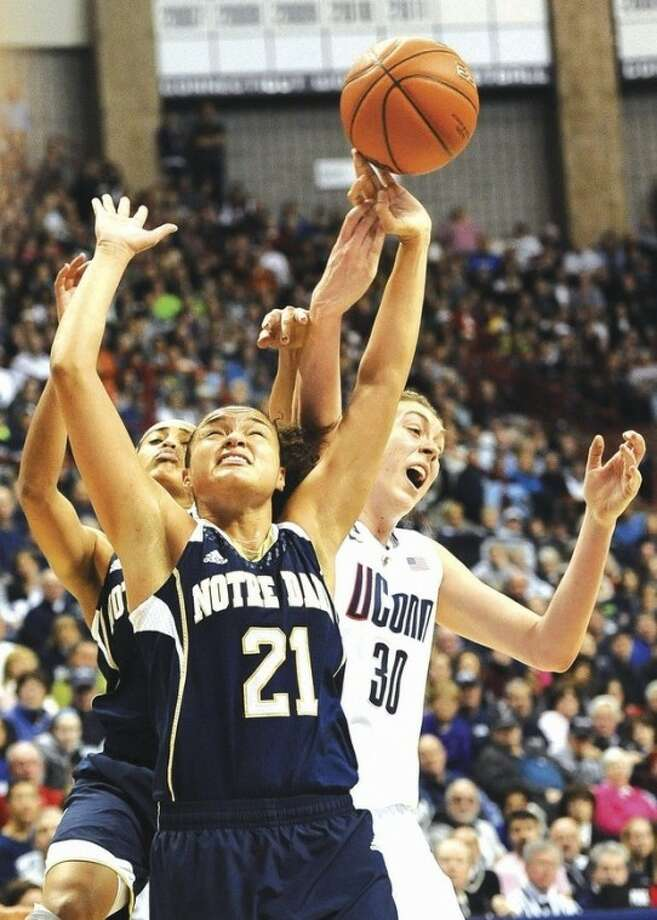 AP photoNotre Dame's Kayla McBride (21) and Skylar Diggins, back left, fight for possession of the ball against UConn's Breanna Stewart during the second half of Saturday's game at Gampel Pavilion. McBride and Diggins were top scorers for the fifth-ranked Irish with 21 and 19 points, respectively, in their 73-72 upset of No. 1 UConn.