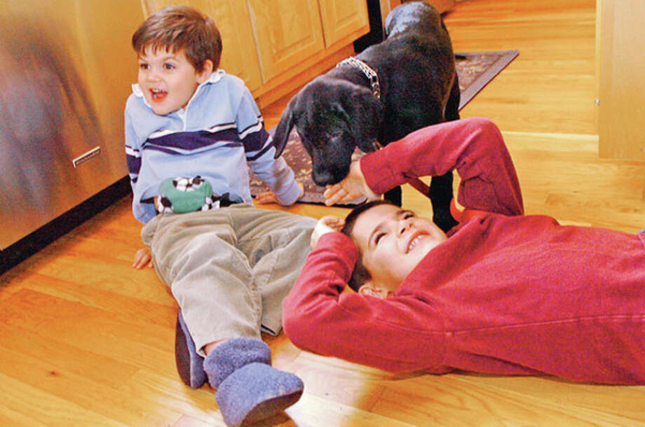 Hour photos / Erik TrautmannAbove, Above, Bryce and Collin Ferguson, 3 and 6, who are diabetic, with their new diabetic alert dog, Ranger. Below, Collin Ferguson, 6, who has diabetes, trains his new diabetic alert dog, Ranger, while a trainer from Guardian Angel Service Dogs, James Falkner, looks on. / (C)2011, The Hour Newspapers, all rights reserved