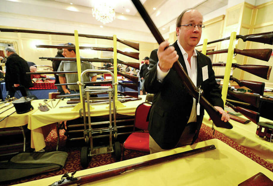 Stuart English displays antique guns at the show. / (C)2012, The Hour Newspapers, all rights reserved