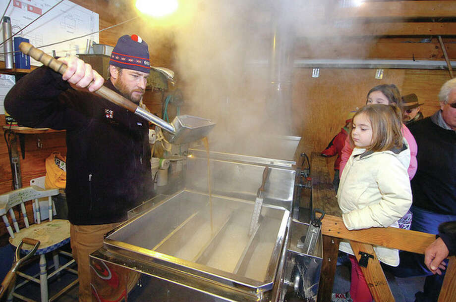 Photo by Alex von KleydorffWill Kies, director of education at the Stamford Museum & Nature's Center, tends to the evaporator inside the nature center's sugar shack on Monday as he discusses the process of making maple syrup. / 2012 The Hour Newspapers