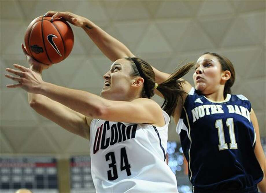Notre Dame's Natalie Achonwa, right, blocks a shot by Connecticut's Kelly Faris during the first half of an NCAA college basketball game in Storrs, Conn., Saturday, Jan. 5, 2013. Notre Dame beat No. 1 UConn 73-72. (AP Photo/Jessica Hill) / FR125654 AP