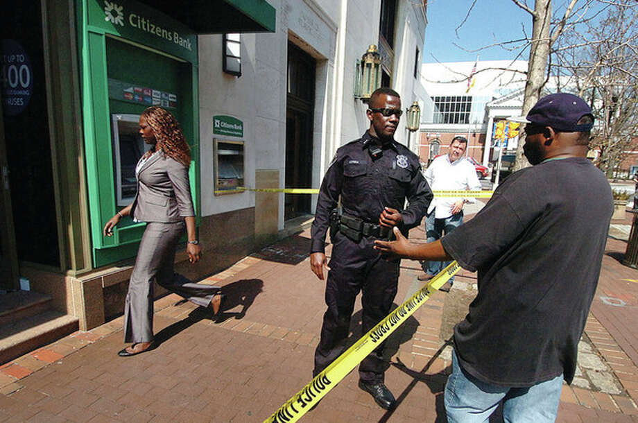 Hour Photo/ Alex von Kleydorff. Police question a possible witness in frnt of the Citizens Bank on Atlantic st Stamford monday afternoon. / © 2012 The Hour Newspapers/Alex von Kleydorff