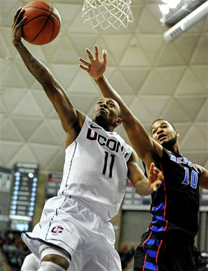 Connecticut's Ryan Boatright (11) goes up for a basket while guarded by DePaul's Derrell Robertson Jr. (10) during the first half of an NCAA college basketball game in Storrs, Conn., Tuesday, Jan. 8, 2013. (AP Photo/Jessica Hill) / FR125654 AP