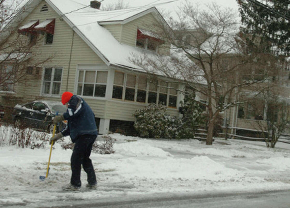 A man shovels the sidewalk on Gregory Boulevard in Norwalk during the snow storm Wednesday afternoon. Hour Photo / DANIELLE ROBINSON