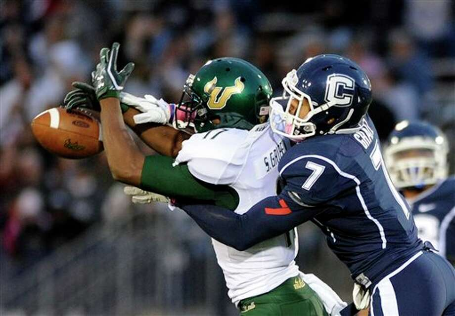 Connecticut's Dwayne Gratz (7) breaks up a pass intended for South Florida's Sterling Griffin, left, during an NCAA college football game in East Hartford, Conn., on Saturday, Oct. 15, 2011. Connecticut won 16-10. (AP Photo/Fred Beckham) / FR153656 AP