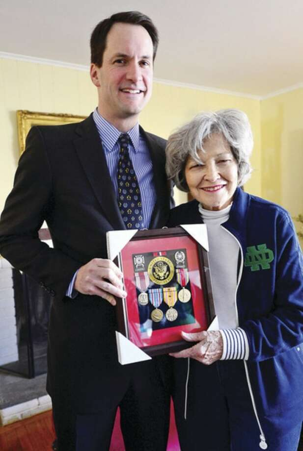 US Congressman Jim Himes delivers eight military service medals to the widow of late U.S. Army Sgt. Clarence Schaffer Jr., Kathleen Schaffer, recognizing the World War II veteran's service as a member of the Parachute Infantry Regiment during a brief ceremony at the Schaffer home Tuesday morning.