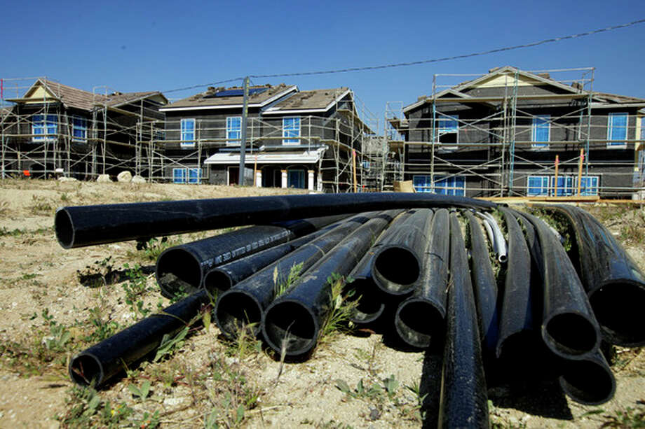 "In this photo taken Thursday, March 15, 2012, PVC pipes are seen next to new single-family detached homes being built by Lennar at the ""Aria at West Creek"" development in Santa Clarita, Calif. U.S. builders started work on slightly fewer homes in February, but they began preparing for what could be the healthiest spring buying season since the housing bubble burst. (AP Photo/Damian Dovarganes) / AP"