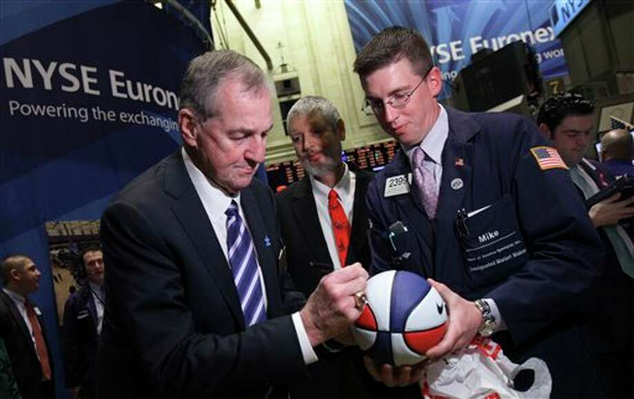 Jim Calhoun, left, head coach of the University of Connecticut's men's basketball team, autographs a basketball for trader Michael Jantz on the floor of the New York Stock Exchange before ringing the opening bell Friday, April 8, 2011. (AP Photo/Richard Drew) / AP