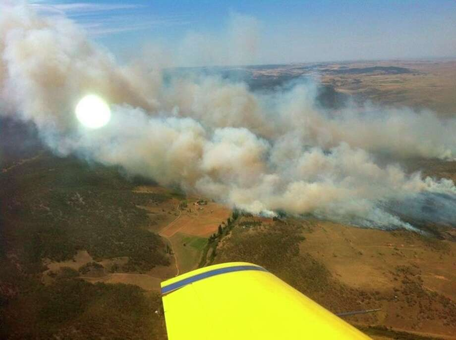 In this photo provided by the New South Wales Rural Fire Service, plumes of smoke rise from a fire near Cooma, Australia, Tuesday, Jan. 8, 2013. Temperatures across much of New South Wales state are expected to reach 45 degrees Celsius (113 degrees Fahrenheit) causing extreme conditions. (AP Photo/New South Wales Rural Fire Service) EDITORIAL USE ONLY / New South Wales Rural Fire Service