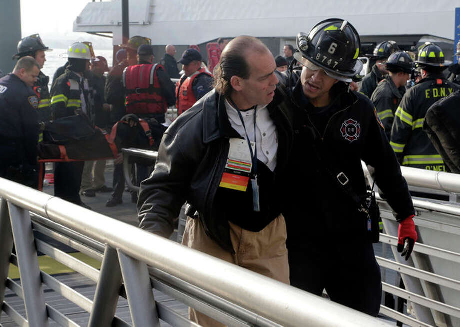 An injured passenger from the Seastreak Wall Street ferry is taken to an ambulance, in New York, Wednesday, Jan. 9, 2013. The ferry from Atlantic Highlands, N.J., banged into the mooring as it arrived at South Street in lower Manhattan during morning rush hour, injuring as many as 50 people, at least one critically, officials said.(AP Photo/Richard Drew) / AP