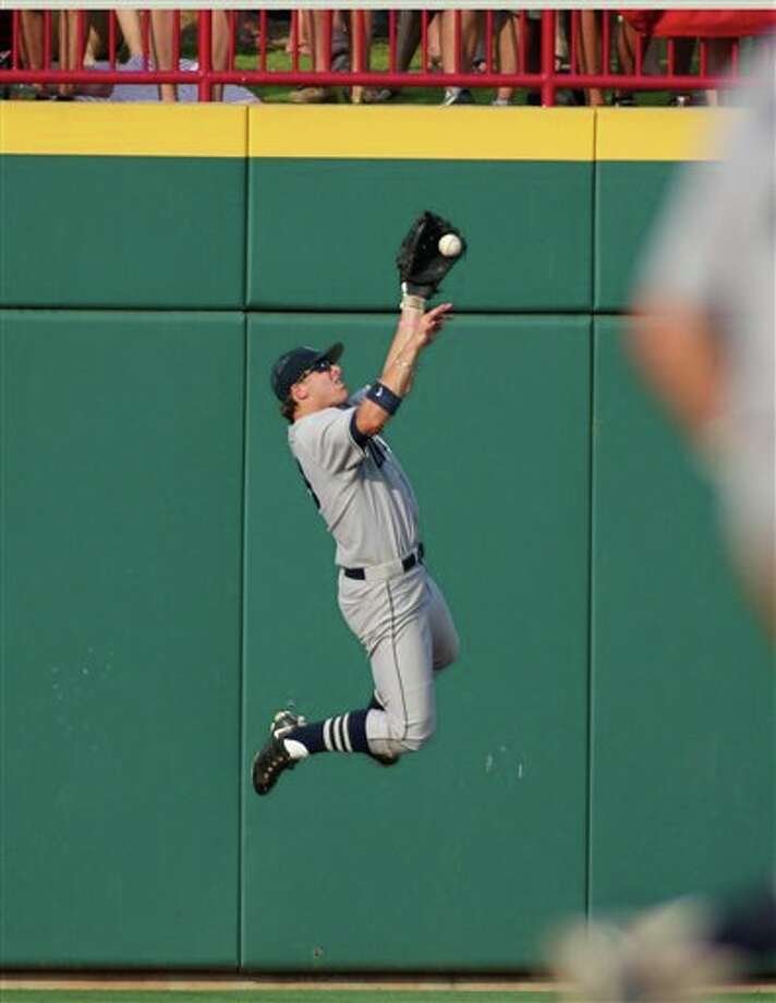 Connecticut right fielder John Andreoli makes a juggling leaping catch against the wall against South Carolina at the NCAA Div. I college baseball super regionals at Carolina Stadium, Saturday, June 11, 2011, in Columbia, S.C.(AP Photo/Willis Glassgow) / fr34287 AP