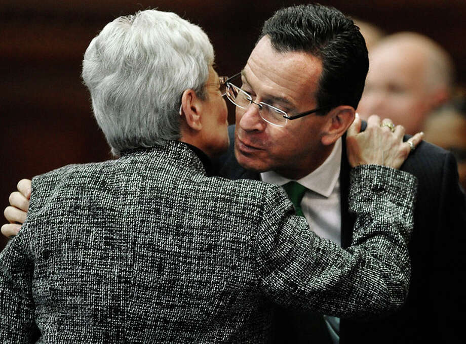 """Connecticut Gov. Dannel P. Malloy, right, is embraced by Lt. Gov. Nancy Wyman, after he is introduced for the State of the State address at the Capitol in Hartford, Conn., Wednesday, Jan. 9, 2013. Malloy urged state lawmakers Wednesday to work with him to prevent future tragedies like the Sandy Hook Elementary School shooting, but stressed that """"more guns are not the answer."""" Legislators also must grapple with a projected deficit of about $1.2 billion. (AP Photo/Jessica Hill) / FR125654 AP"""