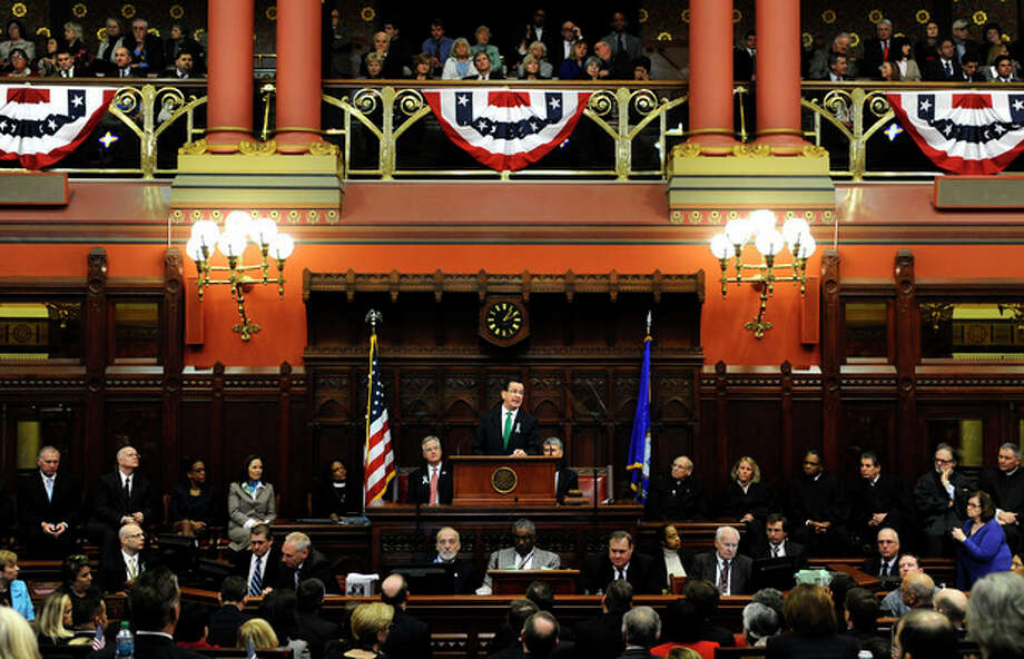 """Connecticut Gov. Dannel P. Malloy, center, at podium, speaks to members of the House and the Senate in his State of the State address at the Capitol in Hartford, Conn., Wednesday, Jan. 9, 2013. Malloy urged state lawmakers Wednesday to work with him to prevent future tragedies like the Sandy Hook Elementary School shooting, but stressed that """"more guns are not the answer."""" Legislators also must grapple with a projected deficit of about $1.2 billion. (AP Photo/Jessica Hill) / FR125654 AP"""