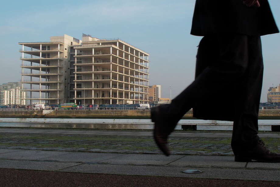 An Irish commuter walks past the abandoned, unfinished headquarters of Anglo Irish Bank in Dublin on Thursday, March 22, 2012. The dead construction site on the River Liffey provides Dubliners a graphic daily reminder of their broken economy. Anglo's reckless lending to construction barons during the Celtic Tiger boom did most to force Ireland to the brink of bankruptcy. Ireland nationalized Anglo and its toxic loan book in 2009 at a cost expected to exceed 47 billion euros ($61 billion) in repayments and interest. (AP Photo/Shawn Pogatchnik) / AP