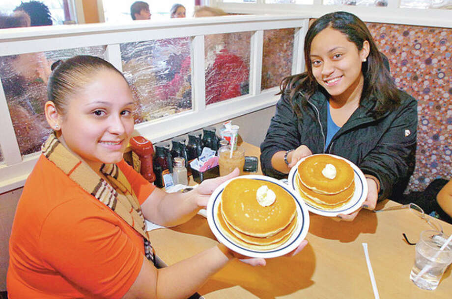 Hour photo / Erik TrautmannAna Quiles and Karina Perez enjoy a free stack at the International House of Pancakes (IHOP) on Summer Street in Stamford Tuesday. / (C)2011, The Hour Newspapers, all rights reserved