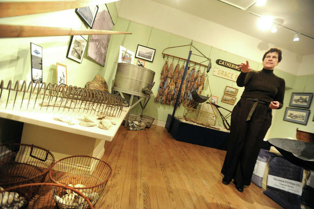 Hour photo/Matthew Vinci Susan Gunn Bromley, curator of the Norwalk Museum, tours the Lockwood Gallery, where the history of oyster fishing is on display Sunday.