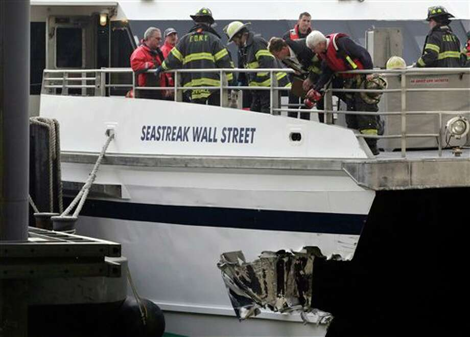 New York City firefighters walk the deck of the Seastreak Wall Street ferry in New York, Wednesday, Jan. 9, 2013. The ferry from Atlantic Highlands, N.J., banged into the mooring as it arrived at South Street in lower Manhattan during morning rush hour, injuring as many as 50 people, at least one critically, officials said.(AP Photo/Mark Lennihan) / AP