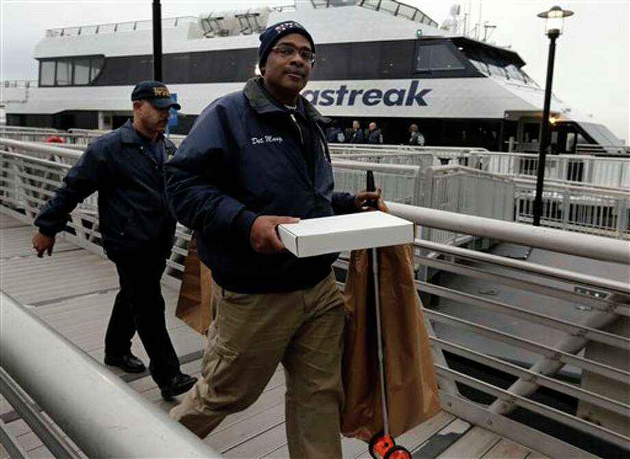 Two members of the New York City Police Dept. Crime Scene Unit carry large paper bags as they leave the Seastreak Wall Street ferry, in New York, Wednesday, Jan. 9, 2013. The Seastreak Wall Street ferry from Atlantic Highlands, N.J., banged into the mooring as it arrived at South Street in lower Manhattan during morning rush hour, injuring as many as 50 people, at least one critically, officials said.(AP Photo/Richard Drew) / AP