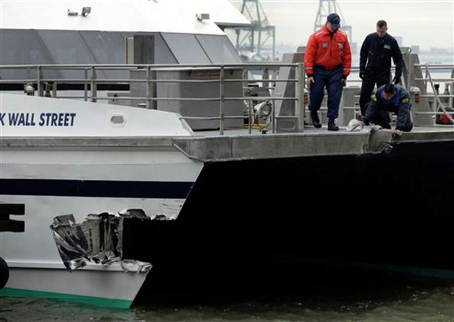 A member of the National Transportation Safety Board, kneeling, and two members of the U.S. Coast Guard, view one of two damaged areas of Seastreak Wall Street ferry, in New York, Wednesday, Jan. 9, 2013. The Seastreak Wall Street ferry from Atlantic Highlands, N.J., banged into the mooring as it arrived at South Street in lower Manhattan during morning rush hour, injuring as many as 50 people, at least one critically, officials said.(AP Photo/Richard Drew) / AP