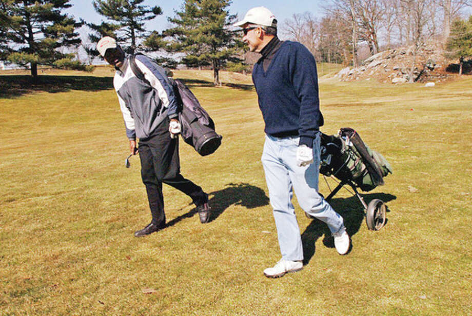 Hour photos / Erik TrautmannAt left, Nick Pisano looks to drive a golf ball at Oak Hills Park Wednesday. At right, Eddie Artis and Chris Salvato head out to play a round for free Wednesday before fees go into effect today. / (C)2011, The Hour Newspapers, all rights reserved