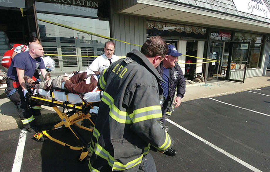A female employee of Hunter Douglas Gallery who suffered injuries when a car smashed into her store is taken to the hospital Monday. / © 2012 Alex von Kleydorff/The Hour Newspapers