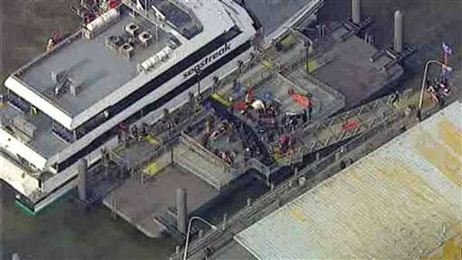 This aerial photo provided by WABC News Channel 7 shows emergency personnel at the scene of a ferry crash in Lower Manhattan, Wednesday, Jan. 9, 2013, in New York. The Fire Department says at least 50 people were injured when a ferry from New Jersey struck a dock during rush hour. (AP Photo/WABC News Channel 7) / 2013 AP