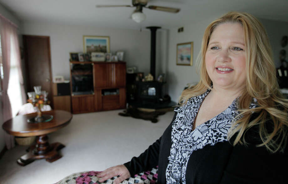 Michelle Chesney-Offutt, poses in her home before leaving for work as an insurance customer service representative, Thursday, March 22, 2012, in Sandwich, Ill. Chesney-Offutt, who was unemployed for nearly three years before landing a job, said a recruiter who responded to her online resume two years ago liked her qualifications and was set to schedule an interview. But he backed away, she said, when he learned she had been out of work for 13 months. The employer he represented would not consider applicants who were unemployed for more than six months, she said. More than a dozen states are considering legislation that would forbid employers from refusing to hire workers just because they've been unemployed for months or years. (AP Photo/M. Spencer Green) / AP