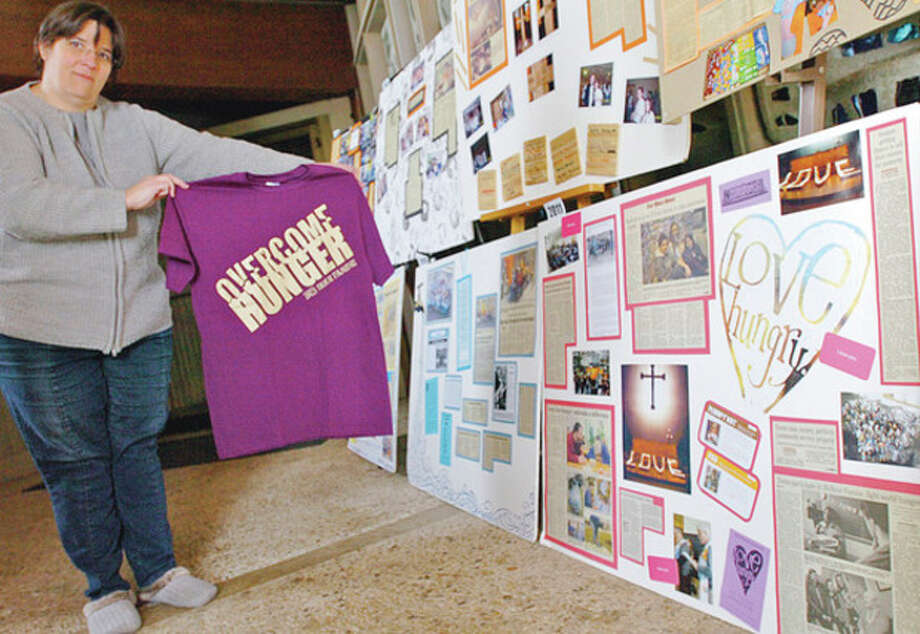 Hour photos / Erik Trautmann Kali DiMarco of the St. Philip Youth Ministry holds a T shirt promoting the ministry's annual 30-hour famine next week to help raise awarness of world hunger. / (C)2011, The Hour Newspapers, all rights reserved