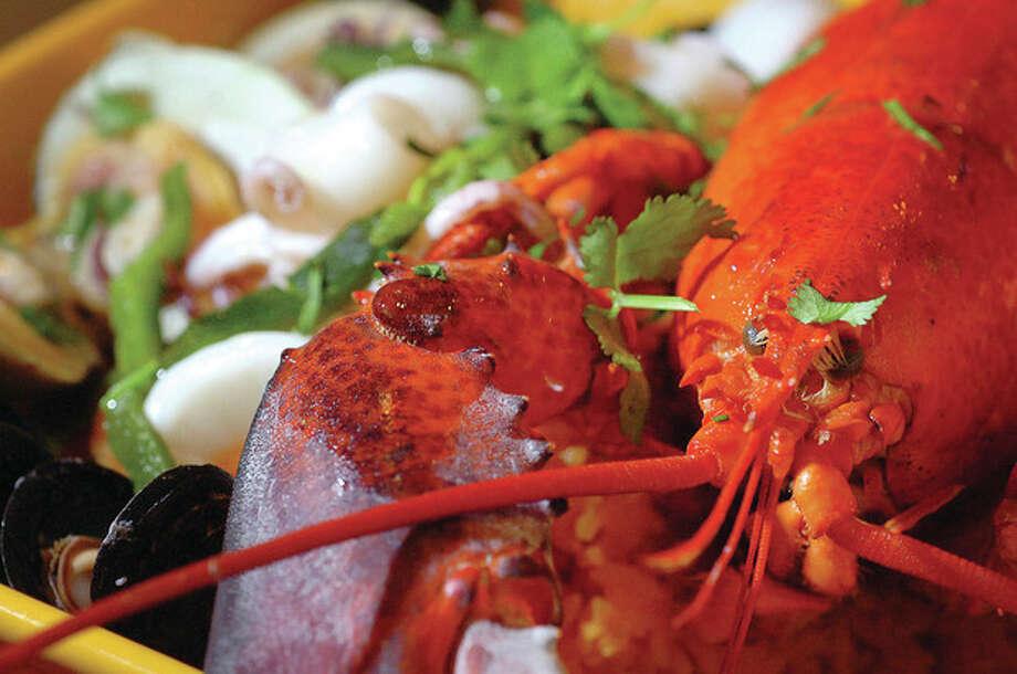 Hour Photo/ Alex von Kleydorff. Paella is fresh made with a whole lobster, mussels, clams, calamari, shrimp and chicken, sausage and saffron rice. / © 2012 The Hour Newspapers/Alex von Kleydorff