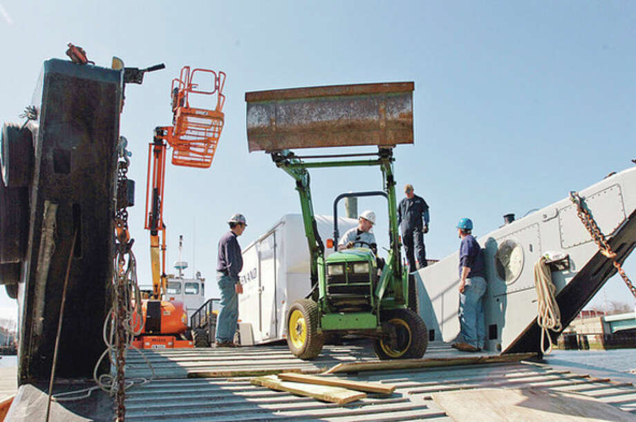 Hour photo / Erik TrautmannWorkers with Cenaxo load construction equipment on a landing craft in Norwalk that will be ferried out to Sheffield Island, where restoration work on the lighthouse and outbuilding begins this week. / (C)2011, The Hour Newspapers, all rights reserved