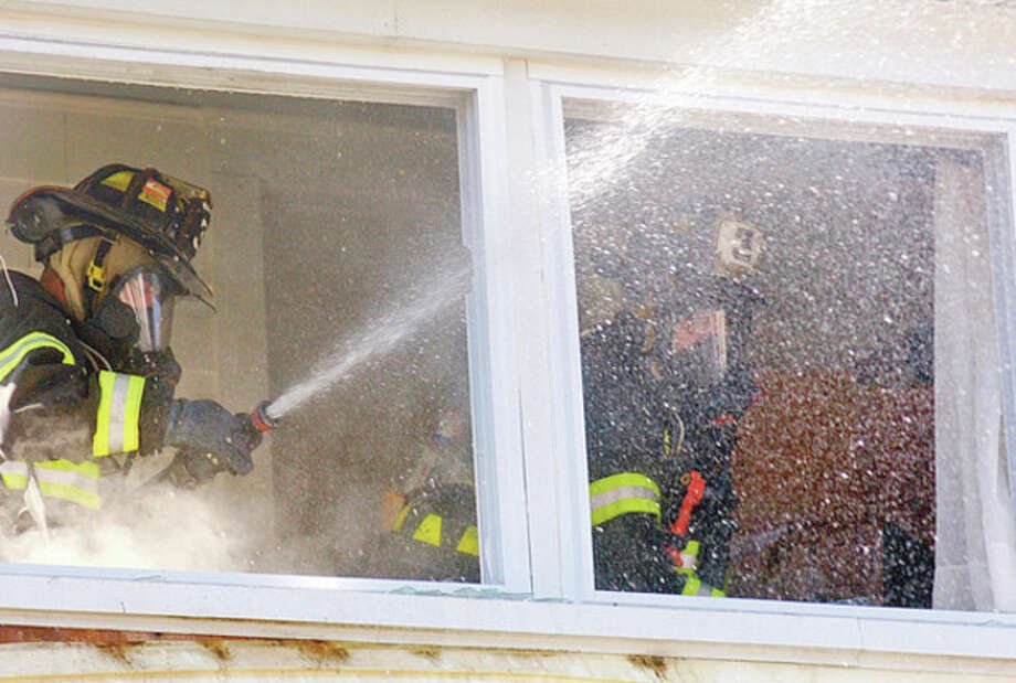 Norwalk firefighters battle a blaze at 14 Gregory Blvd., where a structure fire broke out shortly after noon Tuesday.Hour photo / ErikTrautmann / (C)2011, The Hour Newspapers, all rights reserved
