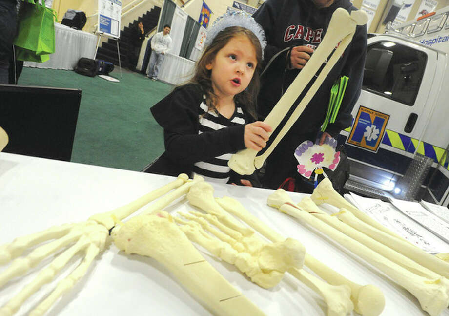 Hour photo/Matthew VinciNoelle Burgess 5, examines various human bones at the Norwalk Hospital physician's table Sunday at the Wilton High School's field house for the WEBE 108/Norwalk Hospital Kids Fest.