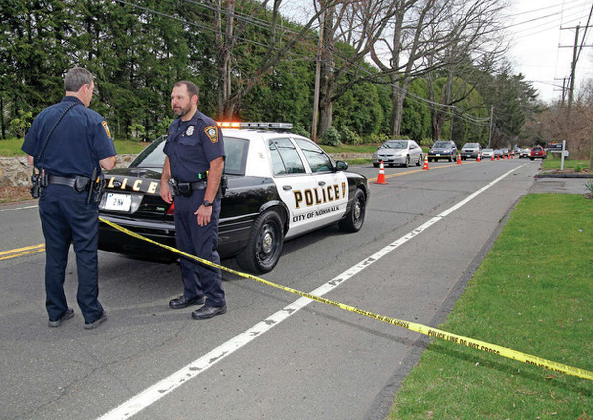 Hour photo / Danielle Robinson Norwalk Police stand at the scene of an accident on New Canaan Avenue where a jogger was struck by a vehicle driven by a 16-year-old girl. He was taken to Norwalk Hospital and later died from his injuries.