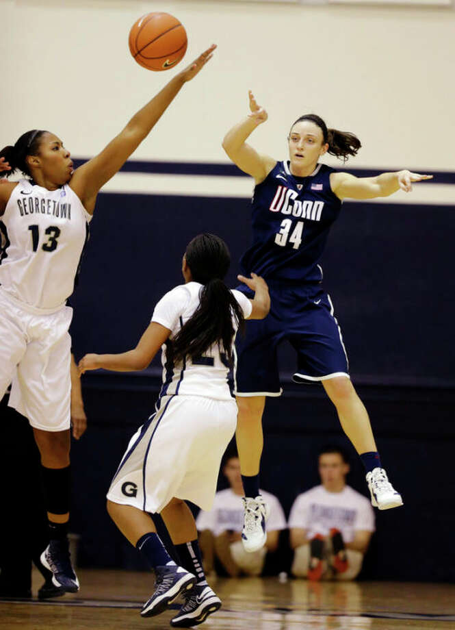 Connecticut guard Kelly Faris (34) passes the ball between Georgetown center Sydney Wilson (13) and guard Samisha Powell (23) during the first half of an NCAA college basketball game, Wednesday, Jan. 9, 2013, in Washington. (AP Photo/Alex Brandon) / AP