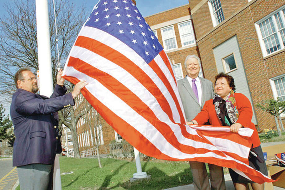 Hour photo / Erik TrautmannNorwalk Recreation and Parks Director Mike Moccaie and Mayor Richard Moccia raise one of the 24 flags the city received from Fran DiMeglio and Northrop Grumman on Wednesday. / (C)2011, The Hour Newspapers, all rights reserved